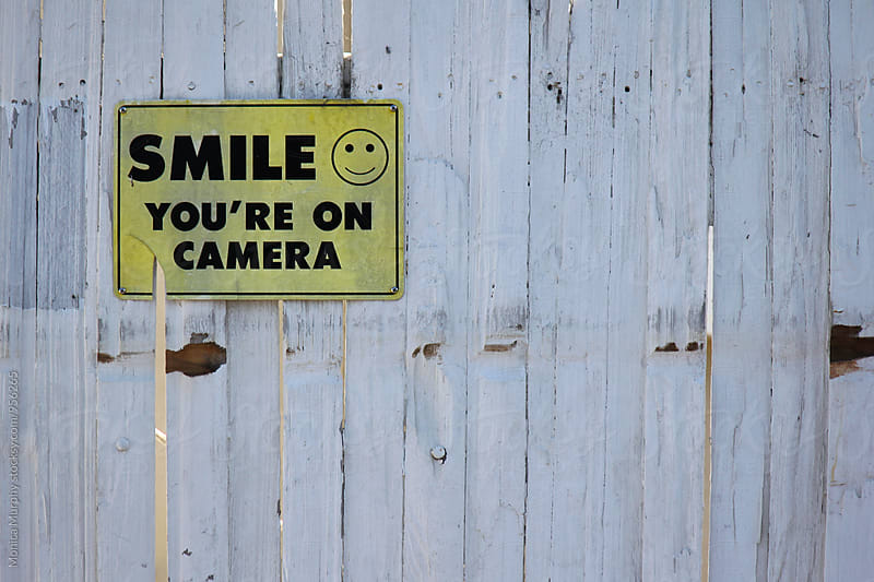 SMILE You're on Camera sign on old fence by Monica Murphy for Stocksy United