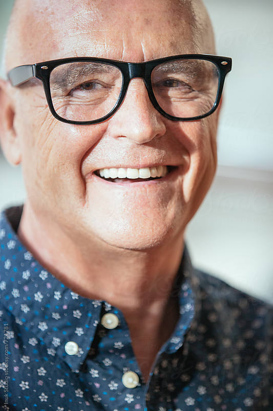 Senior stylish man smiling portrait wearing glasses by Inuk Studio for Stocksy United