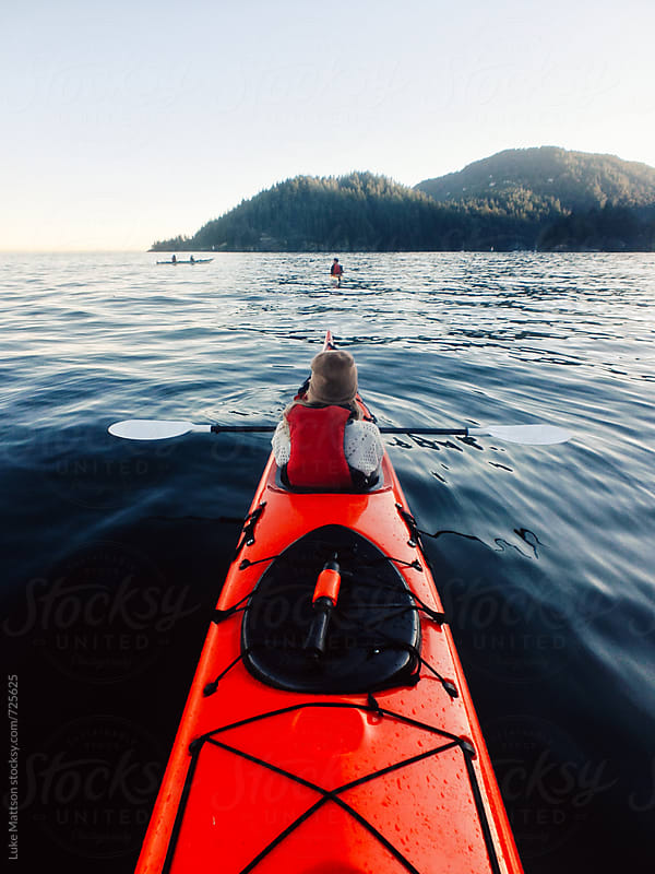 Young Blonde Woman Wearing Life Jacket In Kayak With Paddle On The Pacific Ocean by Luke Mattson for Stocksy United
