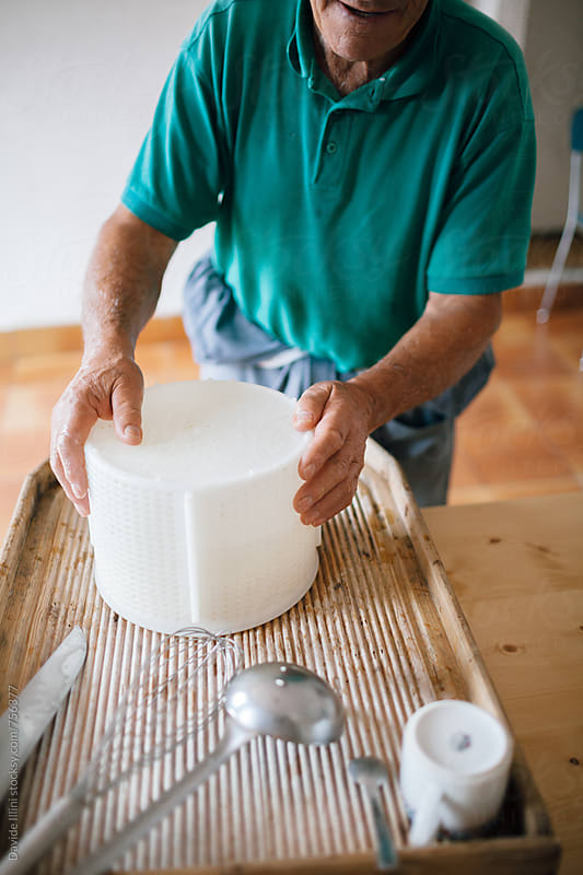 Senior man making homemade cheese by Davide Illini for Stocksy United