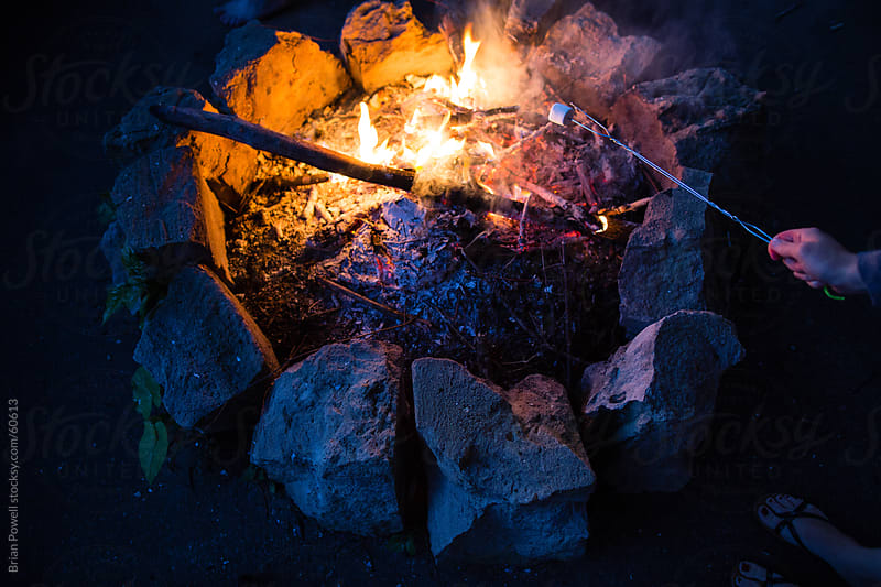 roasting a marshmallow over a campfire at night by Brian Powell for Stocksy United