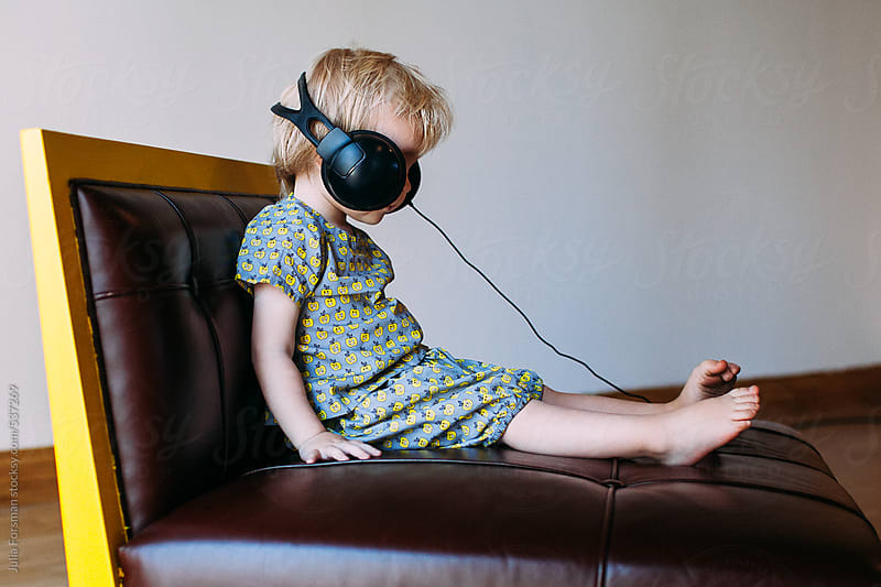 Small child wearing big headphones. by Julia Forsman for Stocksy United
