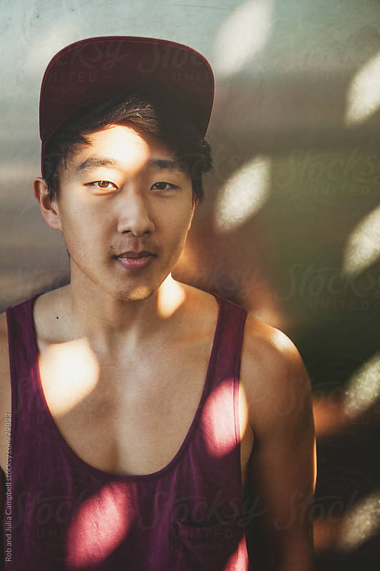 Dappled light on young asian man by Rob and Julia Campbell for Stocksy United