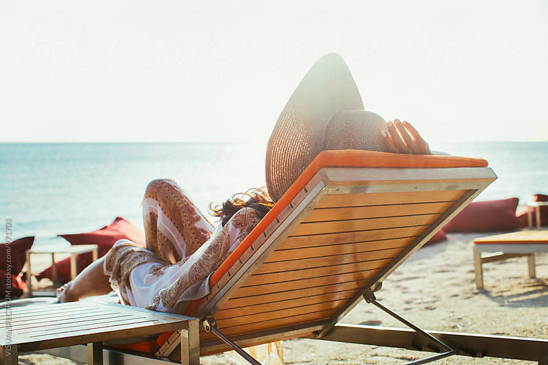 Pretty Young Woman Wearing Large Straw Hat Relaxing on Sunbed on Tropical Beach by VISUALSPECTRUM for Stocksy United