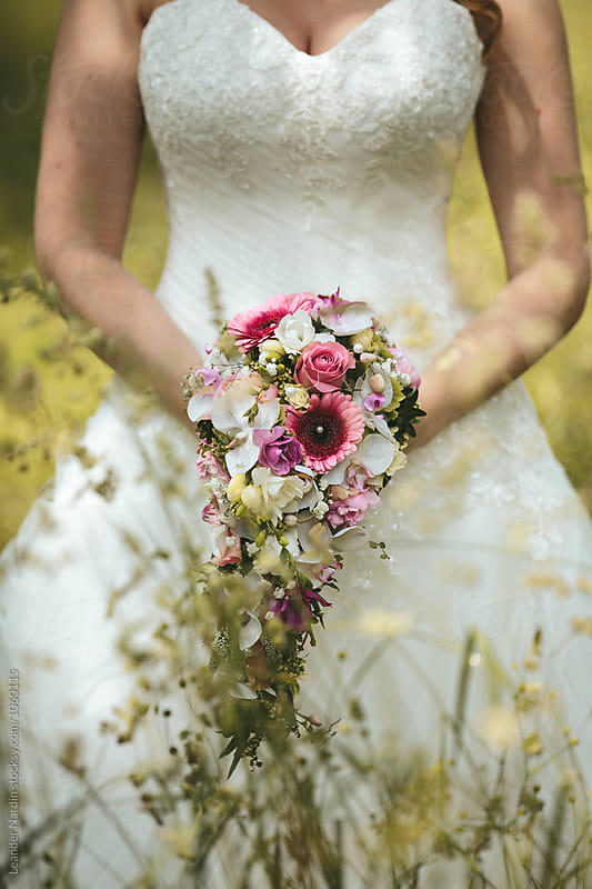 close up of a beautiful bride holding her bridal bouquet by Leander Nardin for Stocksy United