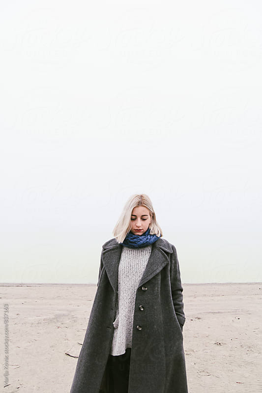 Beautiful blonde woman standing on the beach, vertical by Marija Kovac for Stocksy United