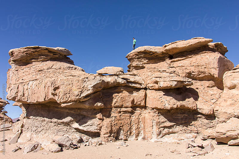 Young man standing on top of a rock formation on desert landscape - Adventure travel by Alejandro Moreno de Carlos for Stocksy United