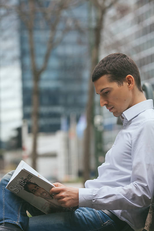 Businessman Reading a Magazine by Mosuno for Stocksy United