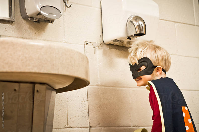 child dressed as superhero playing under hand dryer. by Jess Lewis for Stocksy United