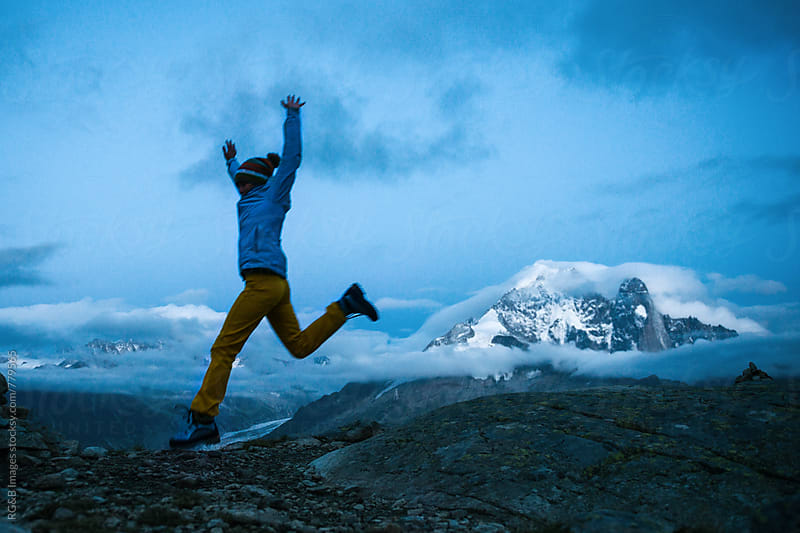 Cheerful hiker jumping in a mountain landscape at dusk by RG&B Images for Stocksy United