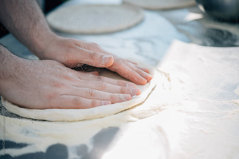 Pizza dough; Making pizza outdoor on a sunny day  by Adrian Cotiga for Stocksy United