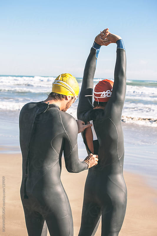 Two triathletes clothing wetsuit and stretching. Ready for swim. by BONNINSTUDIO for Stocksy United