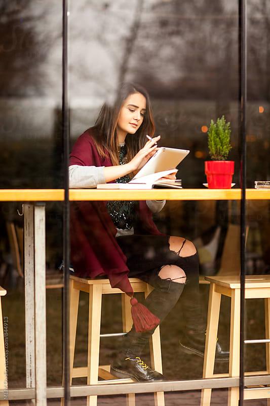 Young brunette sitting inside of a cafe by MEM Studio for Stocksy United