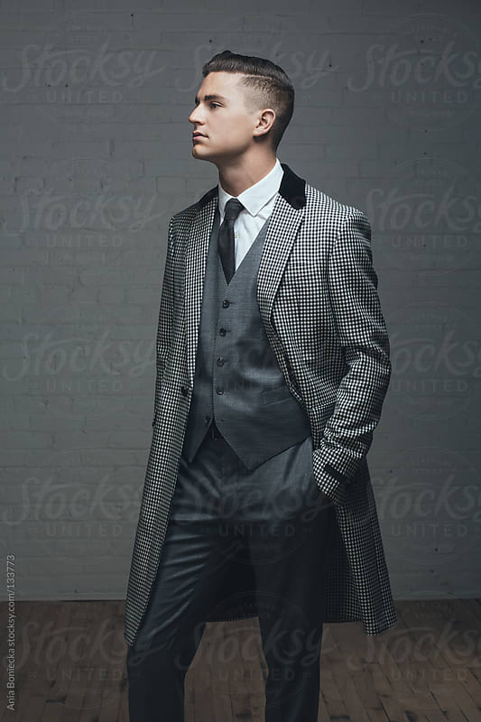 A handsome man in a three piece suit standing with hand in pocket by Ania Boniecka for Stocksy United