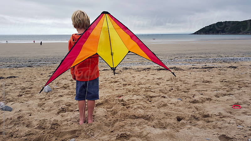 Child stood on the beach holding a kite by sally anscombe for Stocksy United