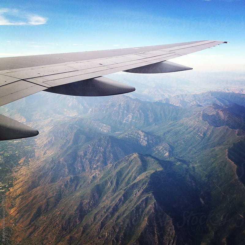 airplane wing shot from a plane over mountains by B. Harvey for Stocksy United