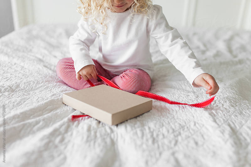 Young girl wearing red and white striped Christmas pajamas open gift box by Amanda Worrall for Stocksy United