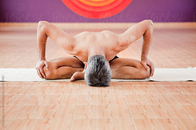 Man doing yoga in a studio by Christine Love Hewitt for Stocksy United