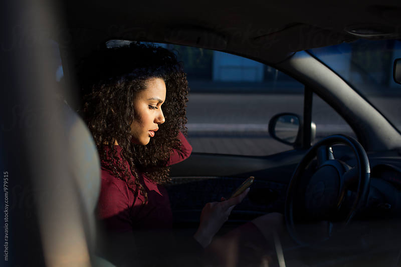 Young woman checking her cell phone sitting inside a car by michela ravasio for Stocksy United