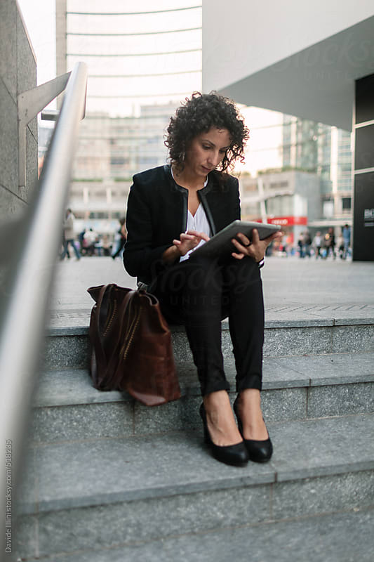 Businesswoman using a digital tablet in the financial district by Davide Illini for Stocksy United