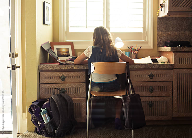 Young girl doing her homework at a desk in the kitchen after school by Carolyn Lagattuta for Stocksy United