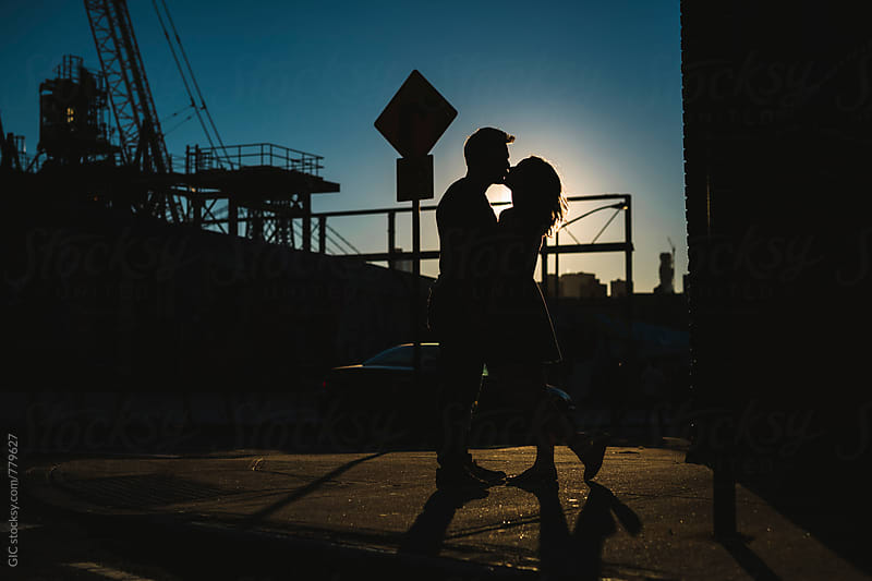 Young couple silhouette kissing in the city by GIC for Stocksy United