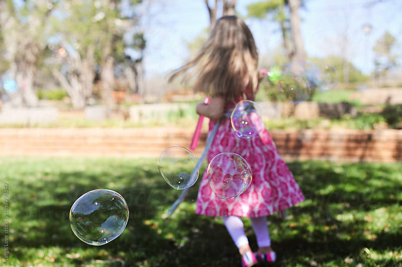 Girl in Pink Dress Twirling While Blowing Bubbles by Leigh Love for Stocksy United
