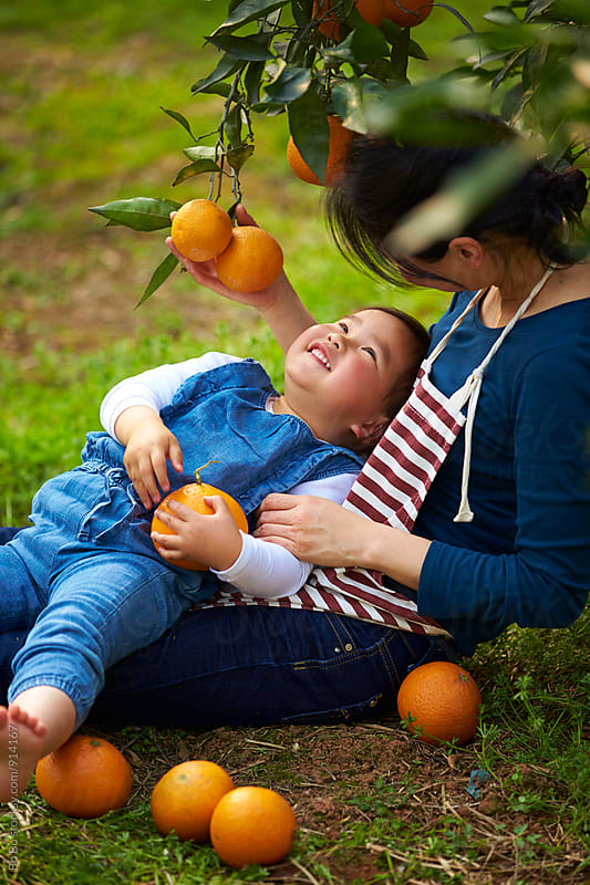 little asian girl with her mother in the orange farm by cuiyan Liu for Stocksy United