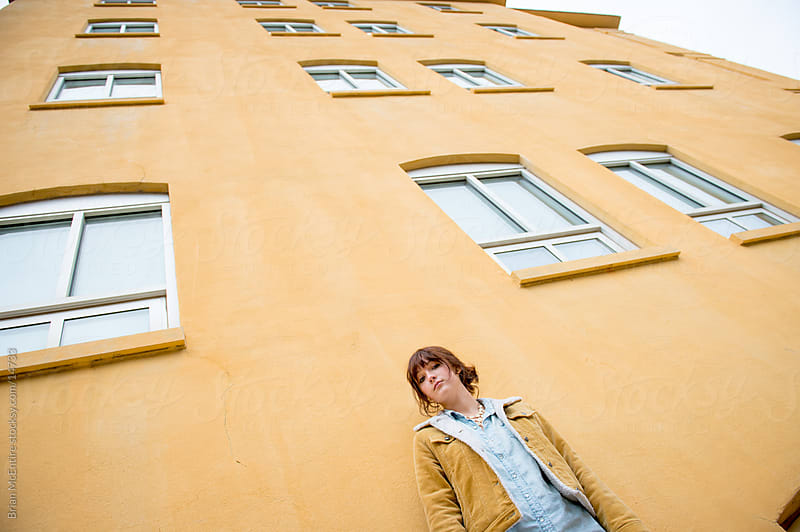 Vintage Young Woman Against Yellow Urban Building by Brian McEntire for Stocksy United