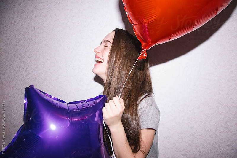 Young brunette laughing while holding two balloons by Danil Nevsky for Stocksy United