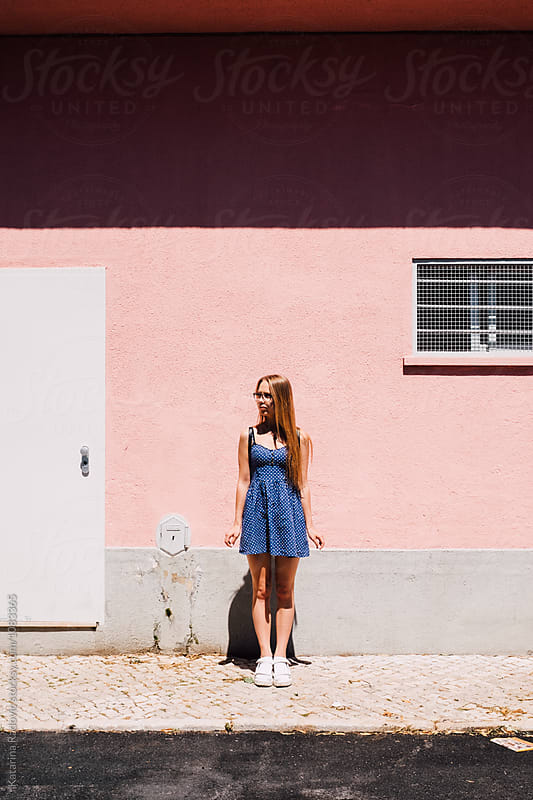 Woman Standing in front of the Pink House by Katarina Radovic for Stocksy United