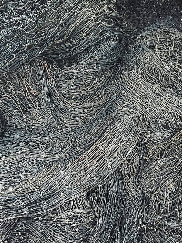 Close up of pile of commercial fishing nets by Paul Edmondson for Stocksy United