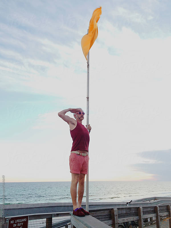 Man saluting next to a yellow beach safety flag by Nicole Mlakar for Stocksy United
