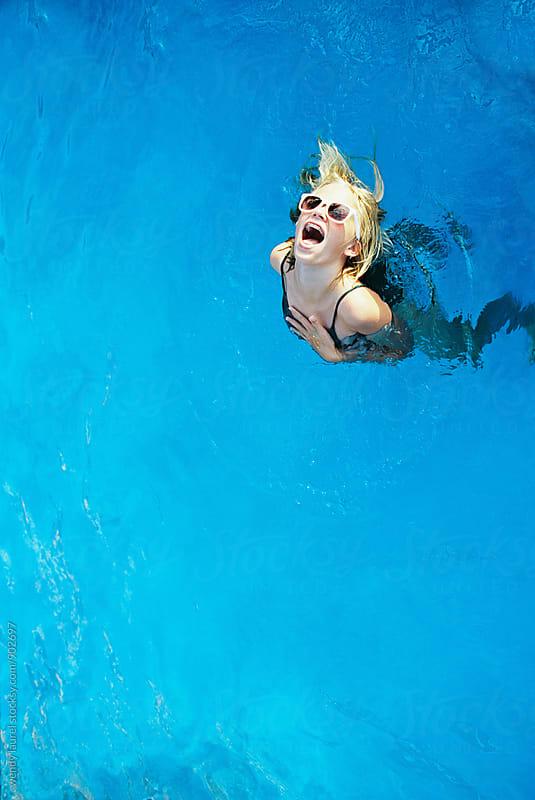 blonde teen girl wearing white sunglasses in very blue pool by wendy laurel for Stocksy United