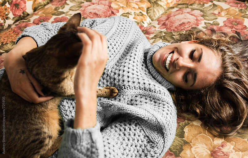 Beautiful girl and her cat playing on bed by Marko Milanovic for Stocksy United