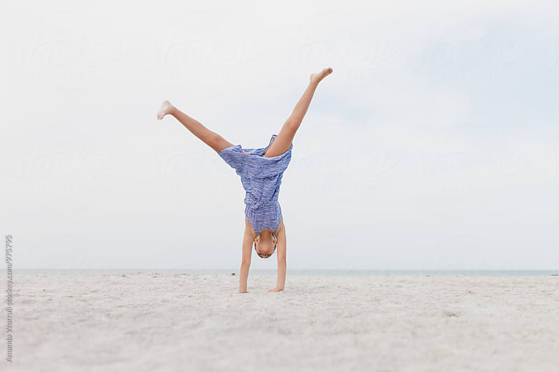 Girl doing a cartwheel on the beach by Amanda Worrall for Stocksy United