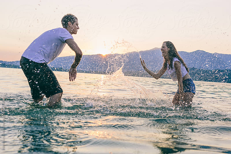 Couple splashing water by michela ravasio for Stocksy United