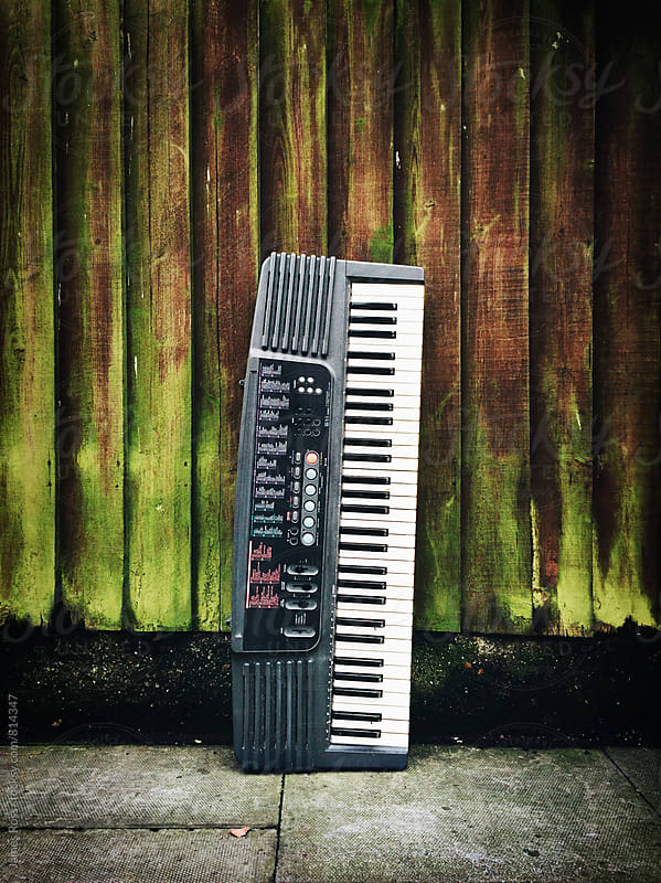 A keyboard propped up against a fence by James Ross for Stocksy United