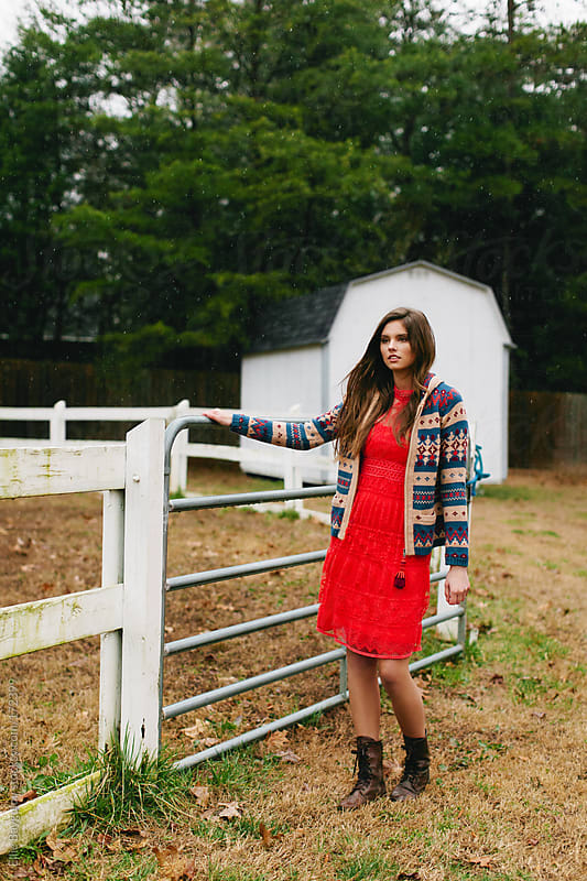 Girl on a farm in a red dress by Ellie Baygulov for Stocksy United