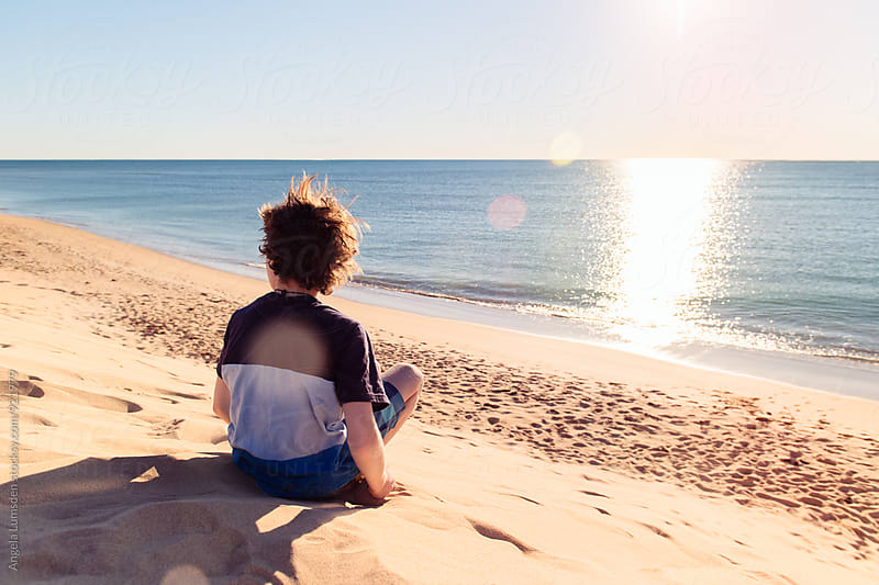 Boy sits contemplating the ocean from a high sand dune as the late afternoon sun sparkles on the water by Angela Lumsden for Stocksy United