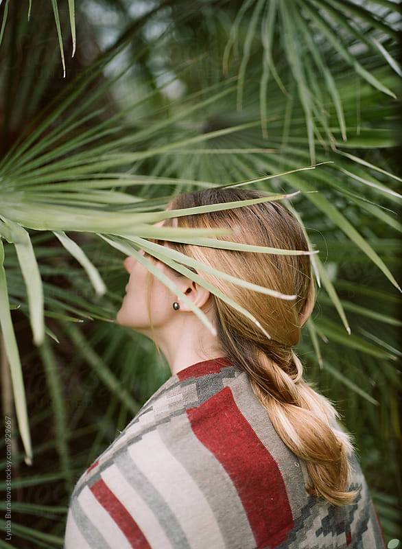 Young woman among palm leaves by Lyuba Burakova for Stocksy United