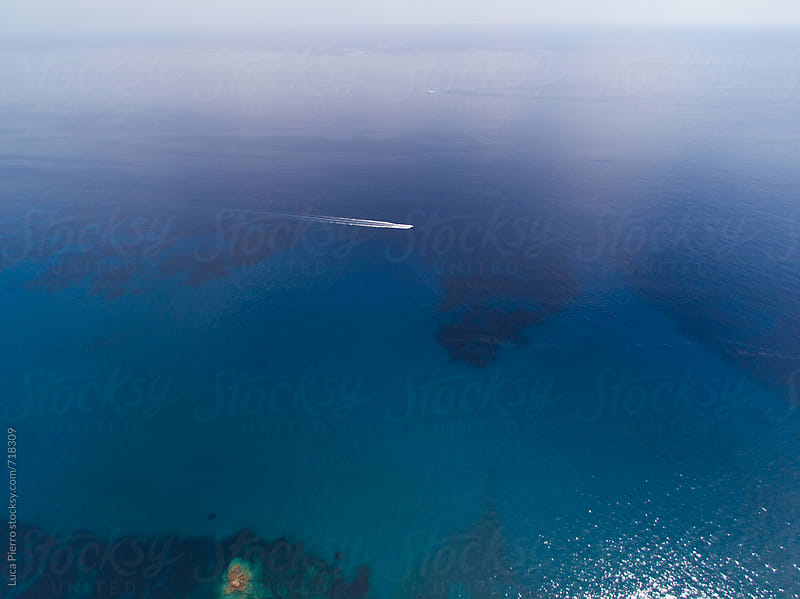 Aerial view of a boat sailing in the mediterranean sea by Luca Pierro for Stocksy United