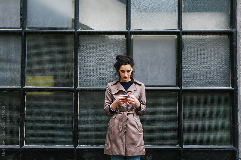 Brunette woman typing on her smart phone by Marija Kovac for Stocksy United