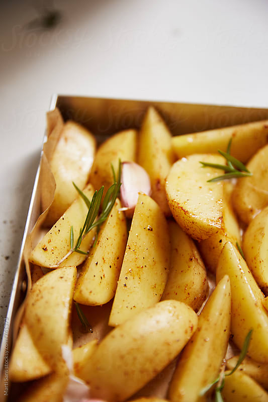 Preparing roast potatoes by Martí Sans for Stocksy United