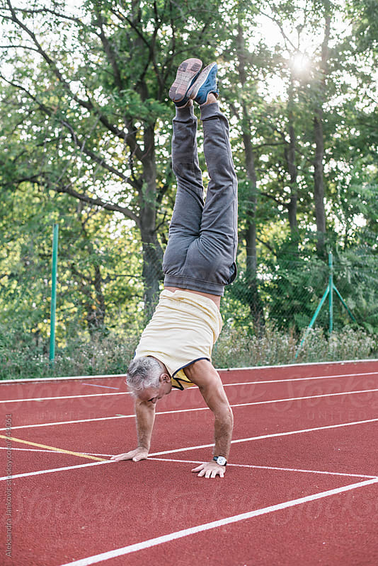 Man Doing Handstand on the Racetrack by Aleksandra Jankovic for Stocksy United
