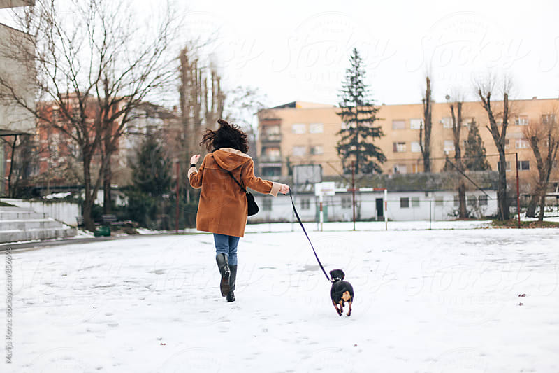 Woman running with her black dog, from behind  by Marija Kovac for Stocksy United