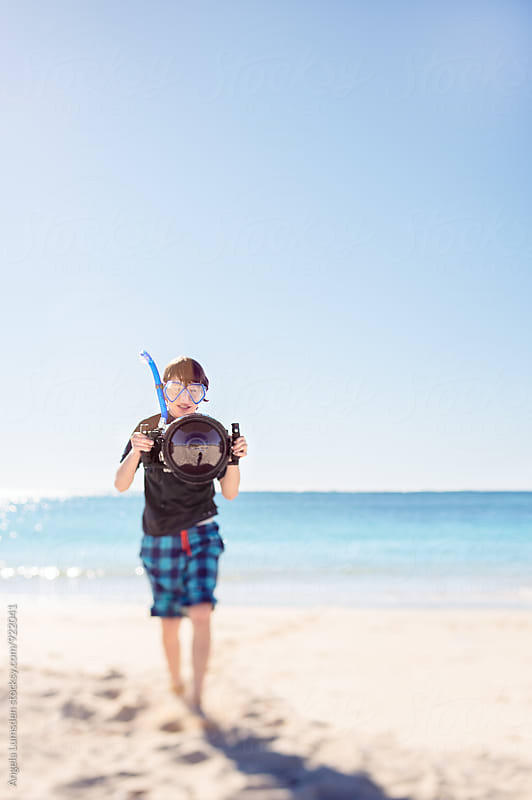Boy returning from snorkeling with underwater camera housing and snorkel set by Angela Lumsden for Stocksy United