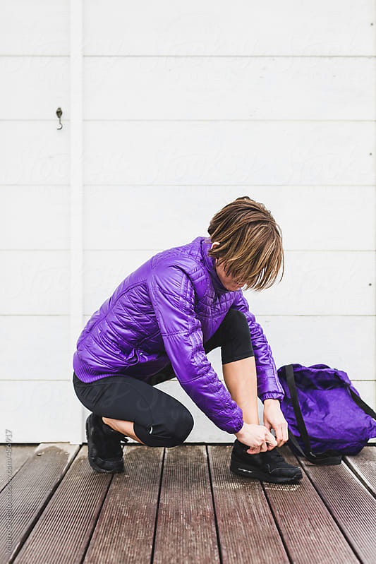 Athletic woman ties his shoes before a workout outdoor by Mauro Grigollo for Stocksy United