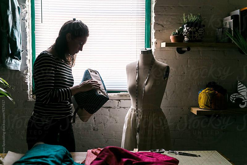 Designer inspecting handbag in studio by Matthew Spaulding for Stocksy United