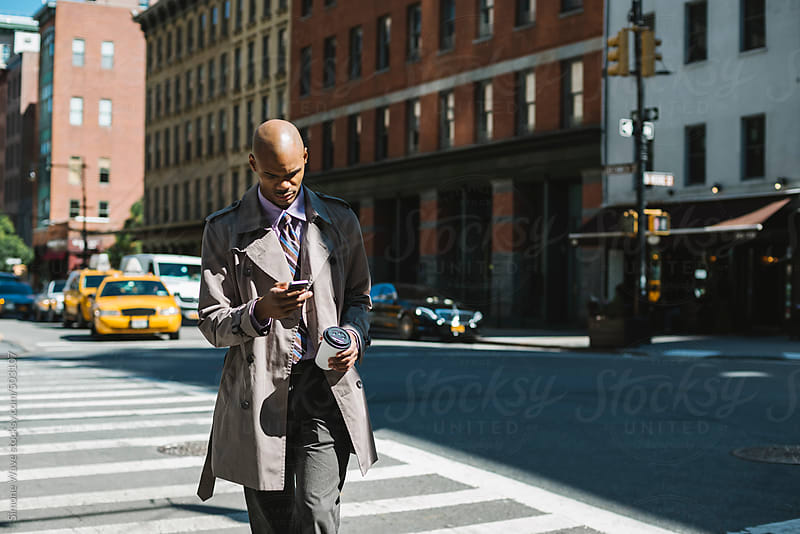 Black businessman walking in the streets of New York City by GIC for Stocksy United